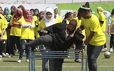 American track and field great Jackie Joyner-Kersee helps a Palestinian woman over a hurdle in the West Bank city of Ramallah, Thursday, April 17, 2014. (photo credit: AP Photo/Nasser Shiyoukhi)