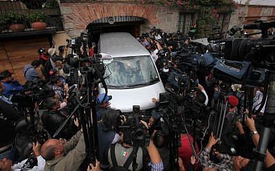 A vehicle from a funeral home is surrounded by journalists as it enters the home of the late Colombian Nobel laureate Gabriel Garcia Marquez in Mexico City, on Thursday, April 17, 2014. (photo credit: AP/Marco Ugarte)