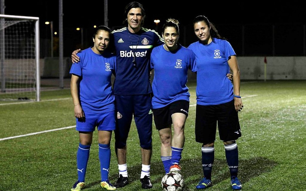 From left to right, Israeli Arab players Hanin Gamal Nasser, Walaa Hussien and Noura Abu-Shanab pose with their coach during a practice session in Petah Tikva, Israel.  (photo credit: AP Photo/Tsafrir Abayov)