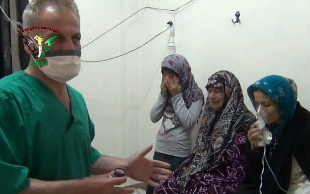 Two women and a young girl are treated by a medic in a rebel-held village in Hama province some 200 kilometers (125 miles) north of Damascus, April 18, 2014.  (photo credit: AP/Shaam News Network)