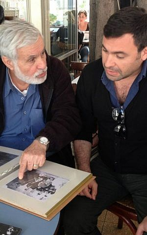 Moshe Zaki shows his son Uri Zaki a scrapbook with photos and articles about his mother Souad Zaki. (photo credit: Renee Ghert-Zand)