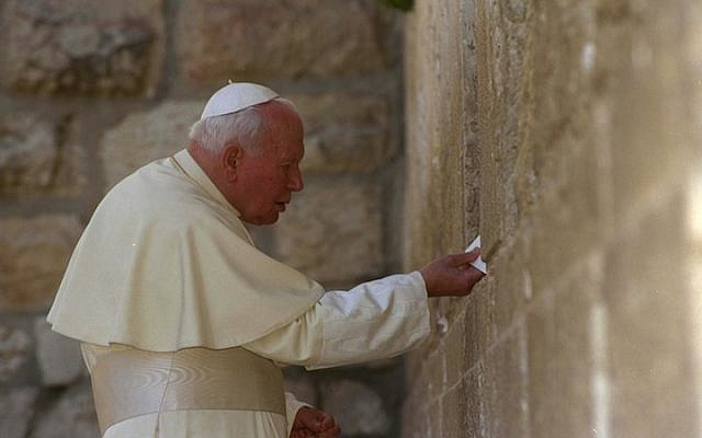 Pope John Paul II places a letter between the stones of Jerusalem's Western Wall on March 26, 2000. (photo credit: Amos Ben Gershom/Israel Government Press Office via Getty Images/JTA)