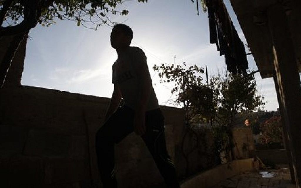 In this Sunday, Nov. 3, 2013 photo, a Palestinian boy walks around his home in the village of Beit Ummar near the West Bank city of Hebron. At the age of 15, the boy was held for nine months in an Israeli military jail for throwing rocks at passing Israeli cars near his village in the West Bank.  (AP Photo/Majdi Mohammed)