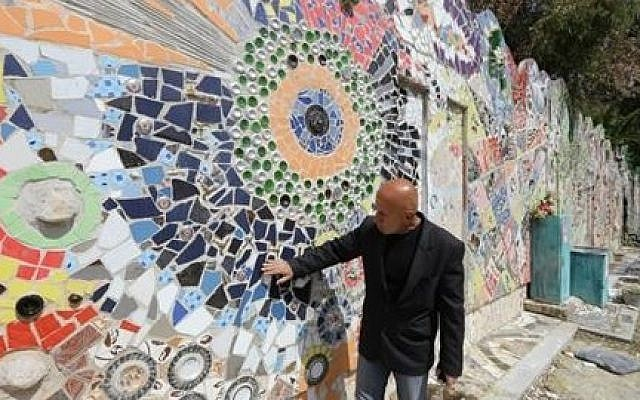 Syrian artist Moaffak Makhoul poses near his decorated wall after it won the Guinness World Records award for the largest mural made from recycled material, on March 31, 2014 in Damascus (Photo credit: Louai Beshara/AFP)