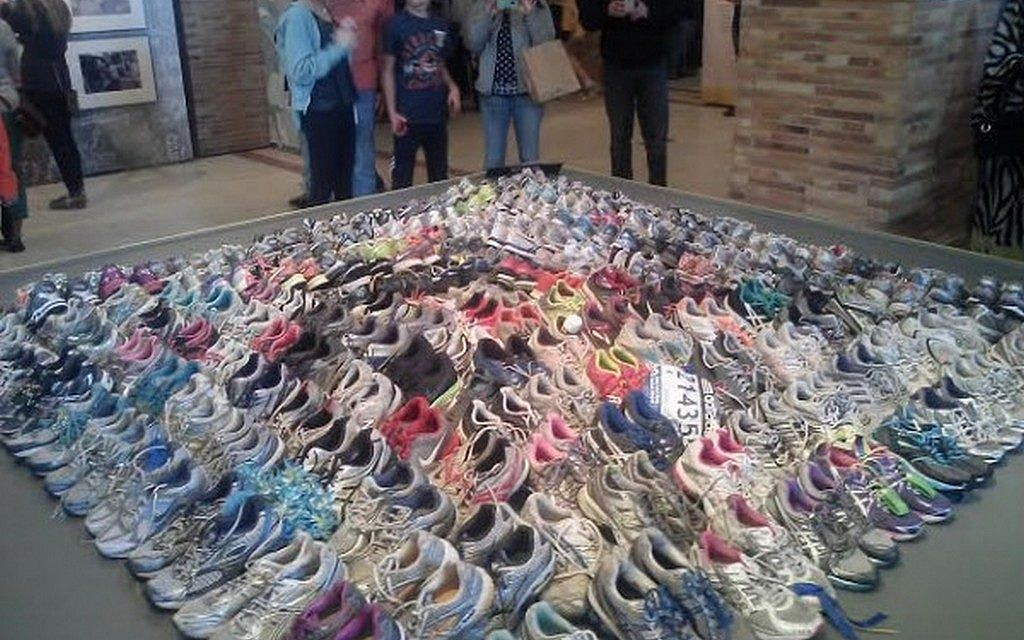 Running shoes left by last year's Boston Marathon runners at makeshift memorials, currently on display at the Boston Public Library (photo credit: Matt Lebovic)