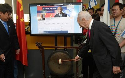 President Shimon Peres strikes a gong at the Beijing ceremony launching his Weibo page (photo credit: Amos Ben Gershom/GPO)