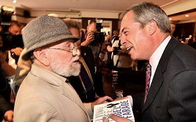 UK Independence Party (UKIP) leader Nigel Farage (R) smiles after signing a copy of his book for a supporter in Basildon in Essex, east of London, on May 23, 2014, as results continue to come in from local council elections in Britain. (photo credit: Ben Stansall/AFP)