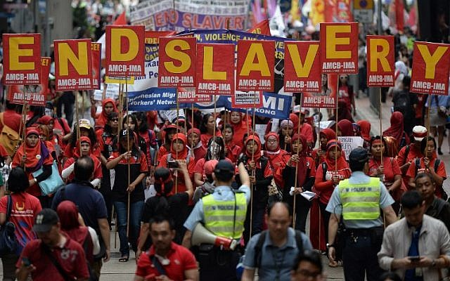 "Migrant workers from Indonesia carry placards which collectively read ""End Slavery"" (top) during a Labour Day rally in Hong Kong on May 1, 2014. (AFP/Anthony Wallace)"