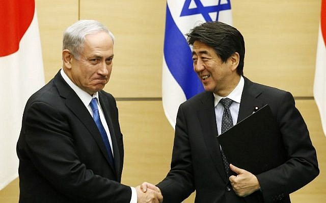 Prime Minister Benjamin Netanyahu (L) shakes hands with Japan's Prime Minister Shinzo Abe after they exchange documents during a signing ceremony at the prime minister's official residence in Tokyo on May 12, 2014 (Photo credit: AFP PHOTO/POOL /Toru Hanai)