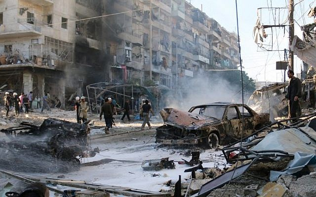 Syrians gather at the site of reported air strikes by government forces on May 1, 2014 in the Halak neighborhood in northeastern Aleppo (photo credit: AFP/AMC/Zein Al-Rifai)