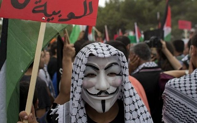 "An Arab Israeli wearing a Guy Fawkes mask takes part in ""The March of Return,"" May 6, 2014 (Photo credit: Ahmad Gharabli/AFP)"