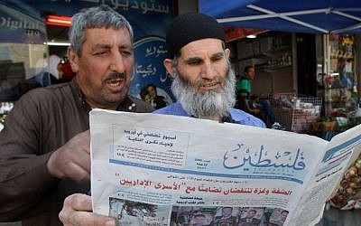 Palestinian men read the Hamas-affiliated newspaper Falastin (Palestine) in a street of the West Bank town of Hebron on May 10, 2014. (photo credit: Hazem Bader/AFP)