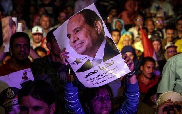 An Egyptian supporter of Egypt's former army chief Abdel Fattah al-Sisi holds his portrait during a gathering in the capital Cairo on May 10, 2014. (photo credit: AFP Photo/Mohamed el-Shahed)