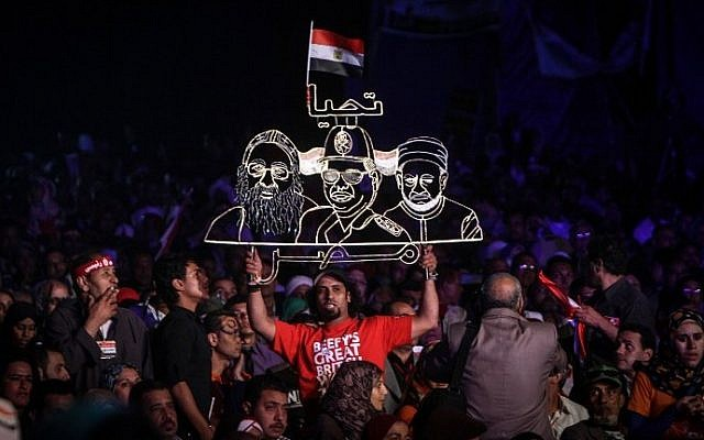 An Egyptian supporter of Egypt's former army chief Abdel Fattah al-Sisi holds a neon sign portraying him (C) along with Pope Tawadros II (L), leader of Egypt's Coptic Church, and Grand Imam of al-Azhar Shiekh Ahmed el-Tayeb (R) during a gathering in the capital Cairo on May 10, 2014. (photo credit: AFP Photo/Mohamed el-Shahed)