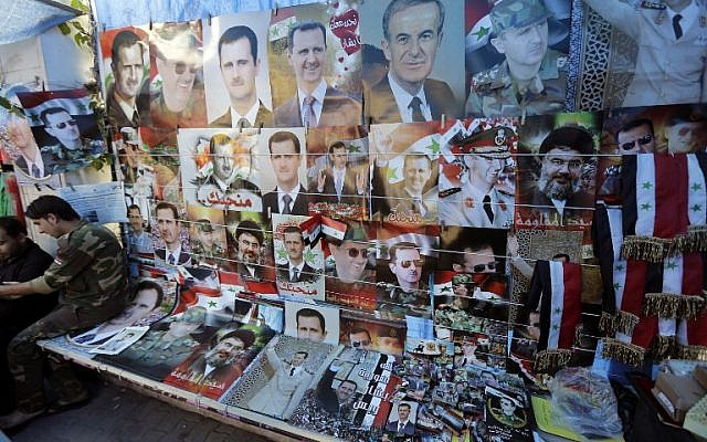 Pictures of President Bashar Assad, his late father and predecessor Hafez Assad, and Lebanese Hezbollah Leader Hassan Nasrallah are displayed at a street shop on May 11, 2014 in the capital Damascus. (photo credit: AFP/JOSEPH EID)