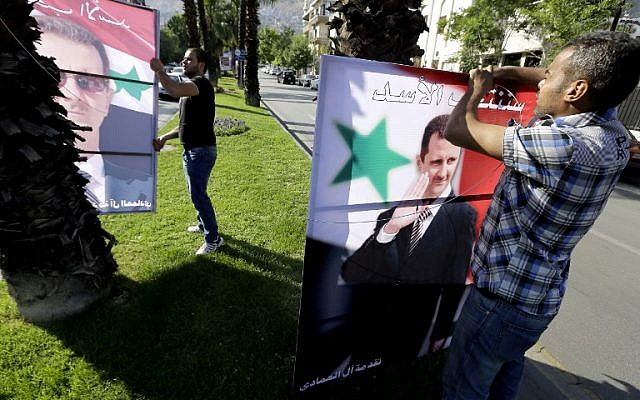 Syrian men hang election campaign billboards bearing portraits of President Bashar al-Assad in a street of the capital Damascus, May 11, 2014. (photo credit: AFP/JOSEPH EID)