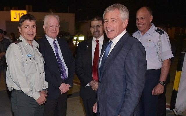 US Defense Secretary Chuck Hagel, 2nd from the right, smiles upon arrival at Ben-Gurion Airport, where he is met by Israeli Major General (ret) Amos Gilad, 2nd from left, US Ambassador to Israel Dan Shapiro, center, and US Defense Attache to Israel, Briggadier General John Shapland, right, on May 14, 2014. (photo credit: AFP/Pool/Mandel Ngan)