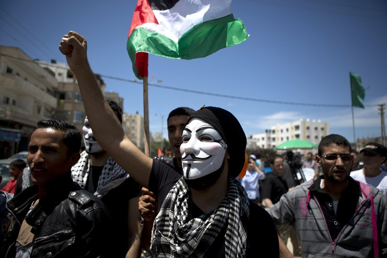 A Palestinian demonstrator wearing a Guy Fawkes mask takes part in a rally near the border with Israel, east of Gaza City on May 15, 2014, to mark Nakba Day (photo credit: AFP/Mohammed Abed)