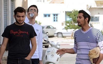 Tunisian Jewish youngsters chat on May 16, 2014 in the Hara Kebira district on the Tunisian island of Djerba, the site of an annual pilgrimage. (photo credit: Fethi Belaid/AFP)
