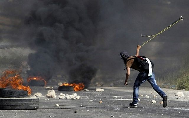 A masked Palestinian demonstrator uses a slingshot to hurl a stone at Israeli security forces outside Ofer prison in the West Bank village of Beitunia, on May 16, 2014. (photo credit: AFP/Abbas Momani)