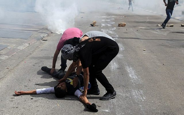 Palestinian demonstrators help an injured friend during clashes with Israeli security forces outside Ofer prison in the West Bank village of Betunia, on Thursday, May 16, 2014 (photo credit: AFP/Abbas Momani)