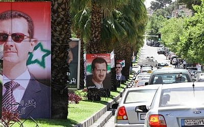 Syrians drive past election campaign posters bearing portraits of President Bashar Assad on May 18, 2014 in the capital Damascus. Campaigning began last week for Syria's June 3 presidential election expected to return Assad to power. (photo credit: Louai Beshara/AFP)