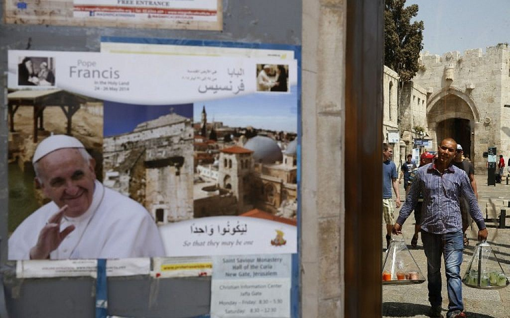 A juice vendor walks past a poster of Pope Francis in Jerusalem's Old City on May 20, 2014 a few days ahead of a the top-level visit by the Pope to the Holy Land. (photo credit: AFP/GALI TIBBON)