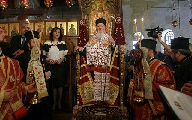 Ecumenical Patriarch of Constantinople Bartholomew I, center, prays at the Church of the Nativity, believed to be the birth place of Jesus Christ, on May 24, 2014 in the West Bank city of Bethlehem. (photo credit: AFP/ MUSA AL SHAER)