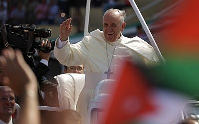 Pope Francis waves to pilgrims upon his arrival at the Amman stadium where he will celebrate a mass on May 24, 2014 in the Jordanian capital. (photo credit: Patrick Baz/AFP)