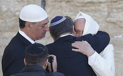 Pope Francis hugs two close Jewish and Muslim friends traveling with him at the Western Wall in Jerusalem's Old City on May 26, 2014. (photo credit: AFP/Thomas Coex)
