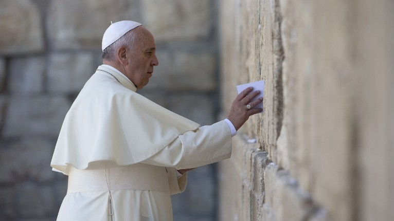 Pope Francis places a prayer paper at the Western Wall, Judaism's holiest site of prayer, in Jerusalem's Old City on May 26, 2014. (photo credit: AFP/Thomas Coex)