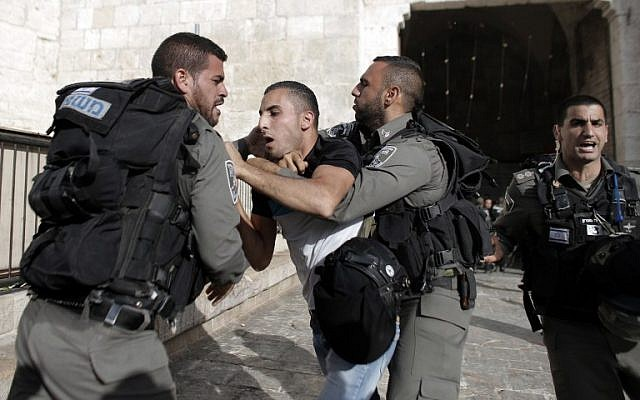 "Border guards detain a Palestinian man as Israelis take part in the ""flag march"" through Damascus Gate in east Jerusalem on May 28, 2014 (photo credit: AFP PHOTO / AHMAD GHARABLI)"