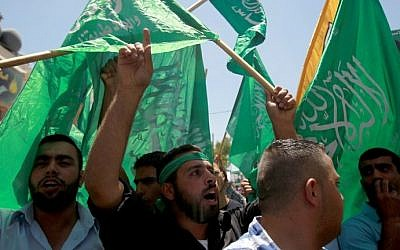 Palestinians in the West Bank wave green Hamas flags during a demonstration in support of Palestinian prisoners on hunger strike in Israeli jails on May 30, 2014. (photo credit: Musa al-Shaer/AFP)