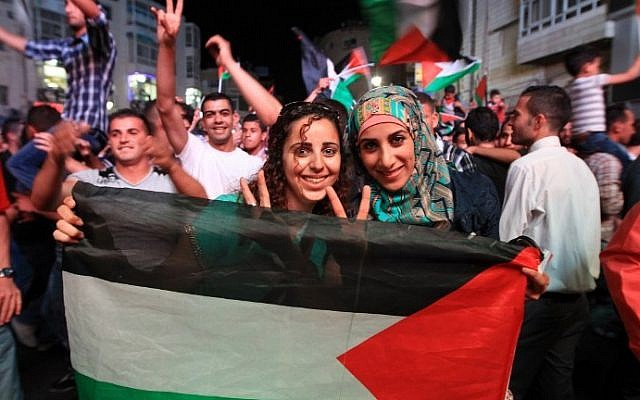 Palestinians celebrate in the West Bank city of Ramallah on May 30, 2014, after Palestine qualified for its maiden Asian Cup appearance with a 1-0 win over the Philippines in the final of the AFC Challenge Cup in Maldives. (photo credit: AFP/Abbas Momani)