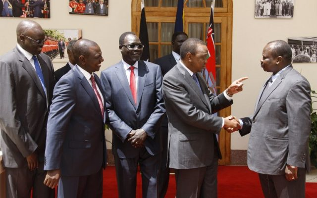 Kenya's President Uhuru Kenyatta (2ndR) shakes hands with South Sudan former secretary-general of the ruling party Pagan Amum (R), on May 8, 2014 in Nairobi, as South Sudan politicians were freed after their trial for treason was stopped in a move seen as a step towards ending brutal civil war. (photo credit: AFP/PSCU)