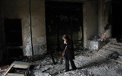 A woman stands on May 10, 2014 in the burned trade union building in Odessa, southern Ukraine, as people gather outside the building during an Orthodox ceremony to mourn the death of pro-Russian militants killed nine days earlier.  (photo credit: AFP/ANATOLII STEPANOV)