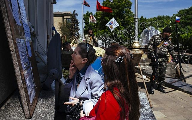 People read information about the forthcoming referendum outside a regional state administration building in the eastern Ukrainian city of Lugansk, on May 10, 2014. (photo credit: AFP/Dimitar Dilkoff)