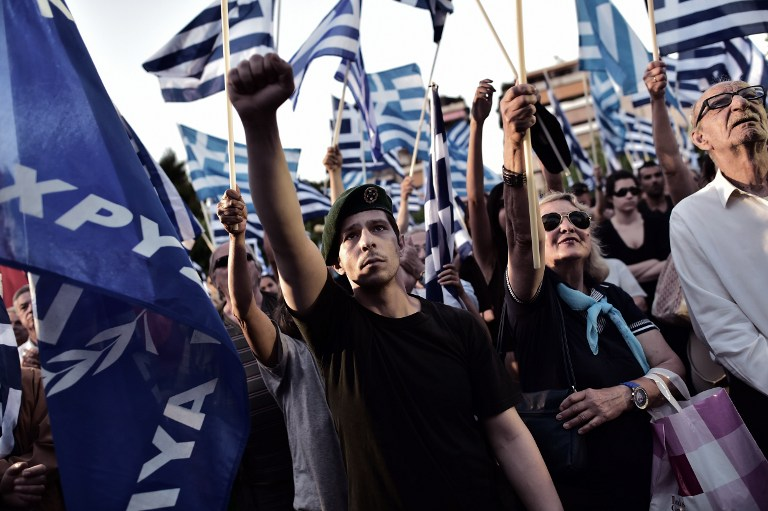 A supporter of the Greek ultra-nationalist party Golden Dawn raises his fist during a preelection rally in Athens on May 23, 2014. (AFP/Aris Messinis)