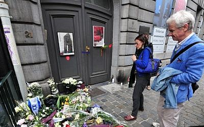 People pay their respects in front of a makeshift memorial at the entrance of the Jewish Museum in Brussels, on May 25, 2014. (photo credit: AFP/GEORGES GOBET)