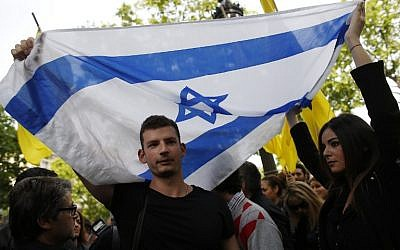 A man and a woman hold an Israeli flag during a demonstration called by French Jewish associations in front of the Belgian Embassy in Paris, on May 25, 2014, to protest against the attack that killed four people the day before at the Jewish Museum in Brussels. (photo credit: AFP/Thomas Samson)