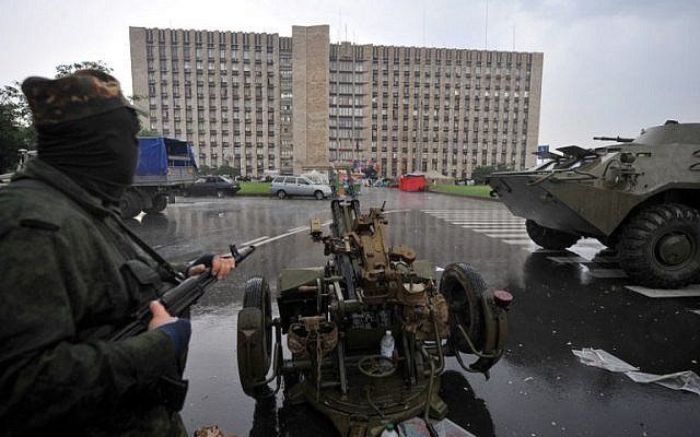 Pro-Russian fighters take their positions before storming the regional state building in the eastern Ukrainian city of Donetsk on May 29, 2014. (photo credit: AFP/ VIKTOR DRACHEV)
