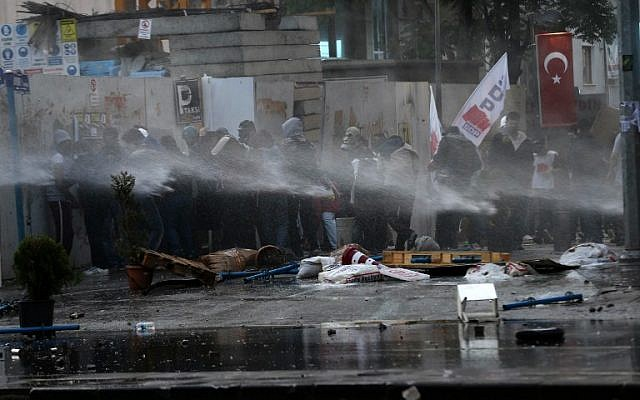 Protesters protect themselves from water cannons and tear gas fired by Turkish riot police on May 31, 2014 in Ankara, as they mark the first anniversary of last year anti-government demonstrations. Photo credit:AFP/ADEM ALTAN)