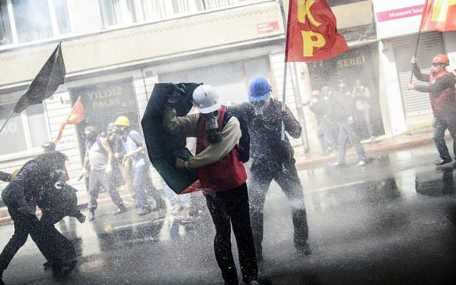 Turkish protesters take cover as riot police use a water cannon to disperse a May Day rally in Taksim Square in Istanbul on May 1, 2014. (AFP/Bulent Kilic)