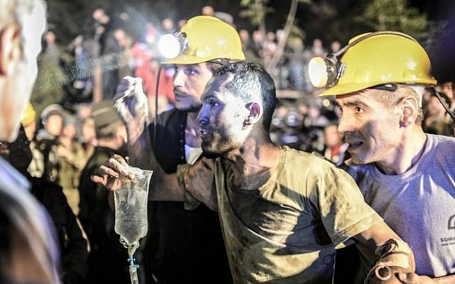 A miner, helped by friends, emerges from a mine after an explosion in Manisa, Turkey, on May 13, 2014. (photo credit: Bulent Kilic/AFP)