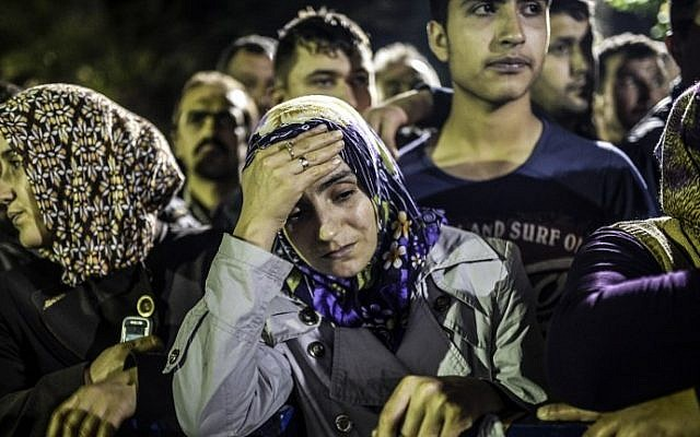 People stand in front of a hospital as they wait for news of their relatives on Wednesday, May 14, 2014. At least 201 people were killed and hundreds more remained trapped underground after an explosion and fire in a coal mine in the western Turkish province of Manisa. (photo credit: Bulent Kilic/AFP)