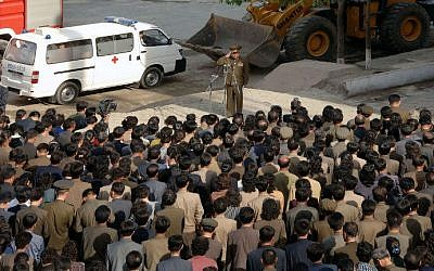 A North Korean construction division officer (top) apologizes to residents following a serious accident in the construction site of an apartment house in Phyongchon District, Pyongyang on May 13. (photo credit: AFP PHOTO / KCNA via KNS REPUBLIC OF KOREA)