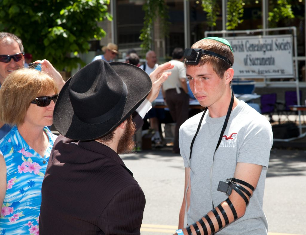 An Orthodox Jewish man helping a Jewish youth put on tefillin (phylacteries). (photo creit: Flickr/Robert Couse-Baker/CCBY-SA)