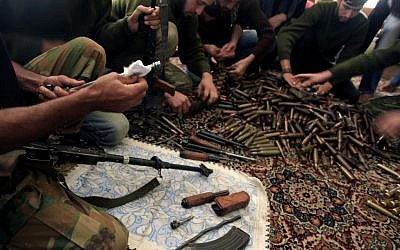 Free Syrian Army fighters clean their weapons and check ammunition at their base on the outskirts of Aleppo, Syria, November 14, 2012 (photo credit: AP/Khalil Hamra)