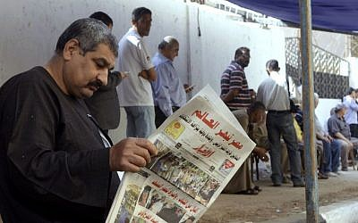 "An Egyptian man reads a local newspaper with the headline in Arabic reading, ""Egypt surprises the world,"" outside a polling station in Cairo, Egypt, Tuesday, May 27, 2014. (AP Photo/Amr Nabil)"