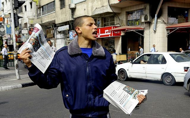 A Palestinian vendor shouts as he sells Al-Quds Newspaper on the first day of its arrival to Gaza from the West bank since being banned by Hamas in 2008, in Gaza City, in the northern Gaza Strip, Wednesday, May 7, 2014. (photo credit: AP Photo/Adel Hana)